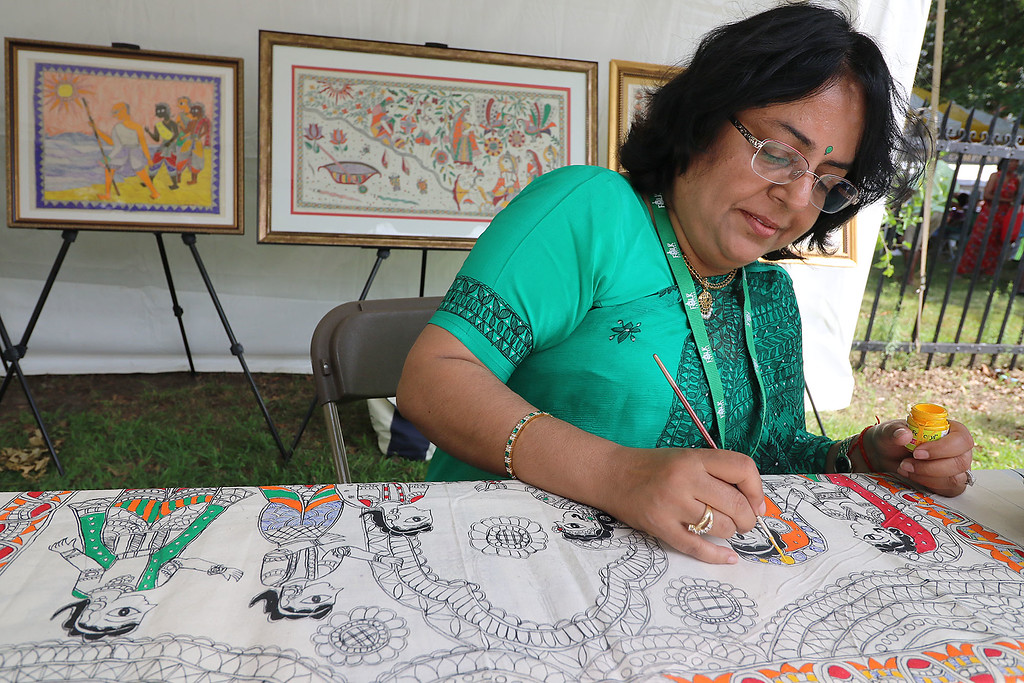 . The last day of 2018 Folk Festival was packed with good food and great performances. Sunanda Sahay works on a painting from north India called Mithila at her booth at the festival on Sunday. SLOWELL SUN/JOHN LOVE