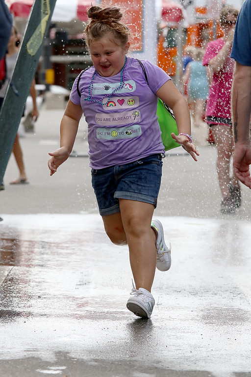 . The last day of 2018 Folk Festival was packed with good food and great performances. It was hot during the last day of the festival so many tried to stay cool like Elanna Rivera, 8, of Nashua by running through the cooling station on Market Street. LOWELL SUN/JOHN LOVE