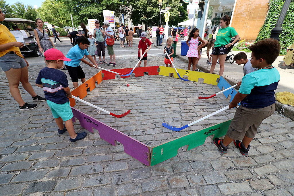 . The last day of 2018 Folk Festival was packed with good food and great performances. Kid play some box hockey on Shattuck Street during the festival. LOWELL SUN/JOHN LOVE