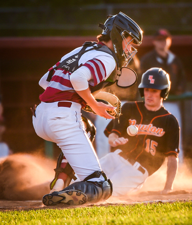 . John Donovan, left, catcher and a Junior with Lowell High, takes a throw at homeplate in the top of the 6th inning, but misses the tag and Tom Byrne of Newton North arrives safe.   Lowell Red Raiders win 7-4.   SUN/Scot Langdon