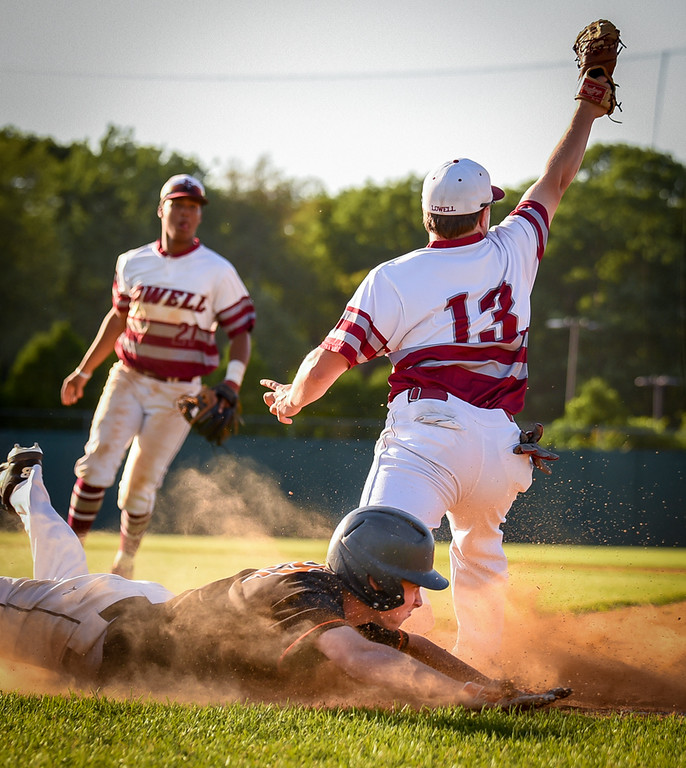 . Lowell High first baseman, Tom Hassett, #13, takes a throw and an out on Newton North player in the top of the second inning Monday.  Lowell Red Raiders win 7-4.   SUN/Scot Langdon