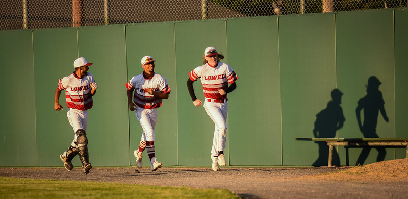 . Chris Ward, center, and fellow Lowell High Varsity baseball teammates, stretch their legs in preparation for Ward to take the mound in later innings to finish the game.   Lowell Red Raiders win 7-4.   SUN/Scot Langdon the