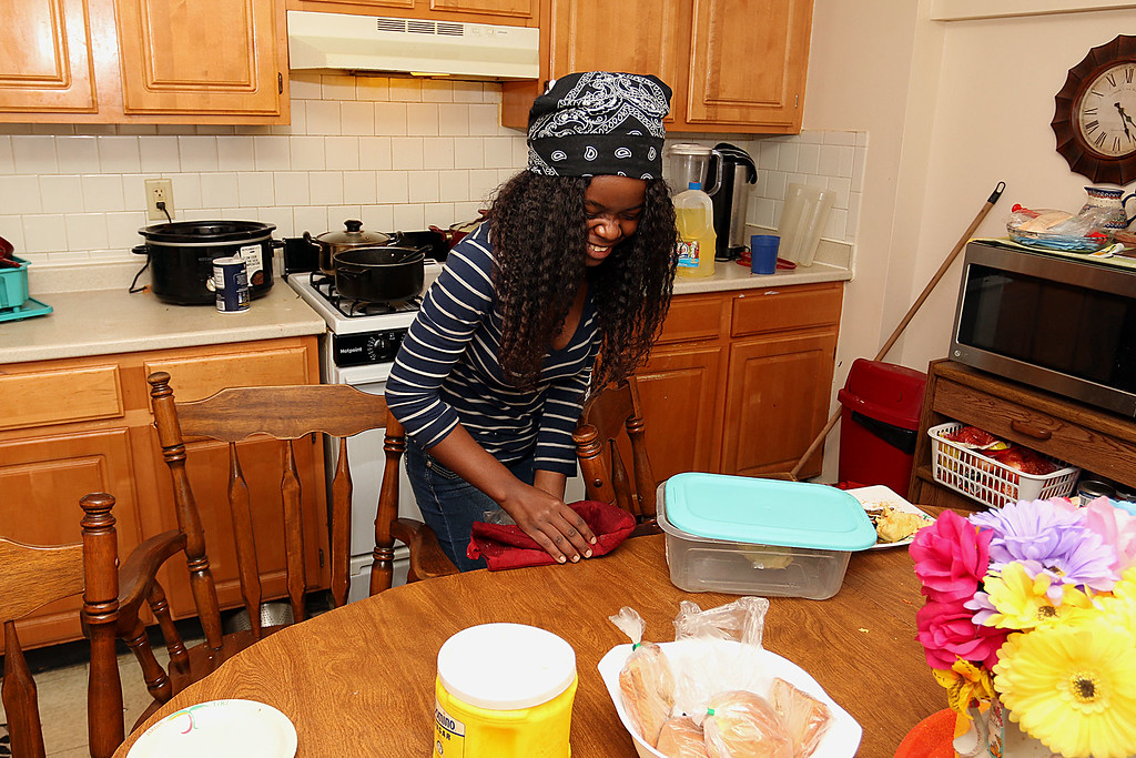 . The Lowell Housing Authority is selling some of its scattered site apartments in order to reduce maintenance costs and generate money to build a new development. Some families are being forced to move because of this. Brigitte Fundu,18, cleans her families kitchen in one Lowell Housing Authority\'s apartments that might be sold. SUN/JOHN LOVE