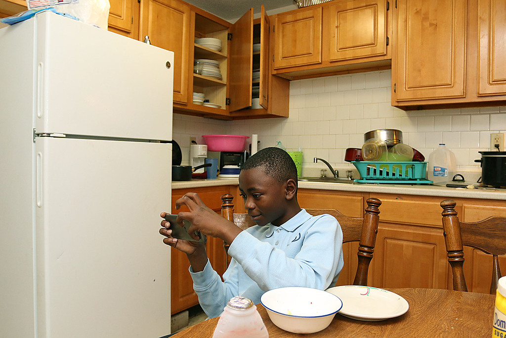 . The Lowell Housing Authority is selling some of its scattered site apartments in order to reduce maintenance costs and generate money to build a new development. Some families are being forced to move because of this. Bisoka Msfiri, 12, hangs out in his kitchen in one Lowell Hosing Authority\'s apartments that might be sold. SUN/JOHN LOVESUN/JOHN LOVE