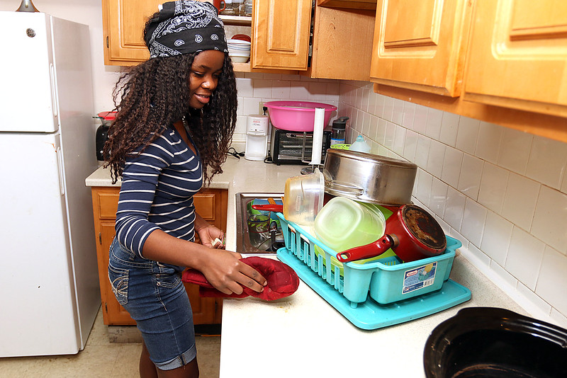 The Lowell Housing Authority is selling some of its scattered site apartments in order to reduce maintenance costs and generate money to build a new development. Some families are being forced to move because of this. Brigitte Fundu,18, cleans her families kitchen in one Lowell Housing Authority's apartments that might be sold. SUN/JOHN LOVE