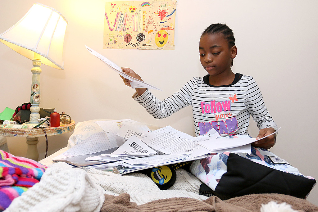 . The Lowell Housing Authority is selling some of its scattered site apartments in order to reduce maintenance costs and generate money to build a new development. Some families are being forced to move because of this. Vumilia Msafiri, 10, works on her homework in her bedroom of one of the Lowell Hosing Authority\'s apartments that might be sold. SUN/JOHN LOVE