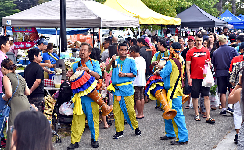Roving musicians make their way through the large number of people at the 23th Lowell Southeast Asian Water Festival. SUN/David H. Brow