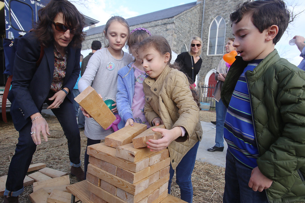 . 2017 Lowell Winterfest Saturday. From left, Stella Mereves-Carolan of Lowell and her nieces Sophia Mereves, 9, Chloe Mereves, 8, of Lowell, and niece Martha and nephew Christofer Kapetanakis, 7 (twins) of Tewksbury, set up for another game of Jenga at Lucy Larcom Park.  (SUN/Julia Malakie)