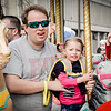 Jeff Huff and his daughter Emma, 2, of Stowe have fun on the carousel at the Lowell Winterfest on Saturday. SUN/Caley McGuane