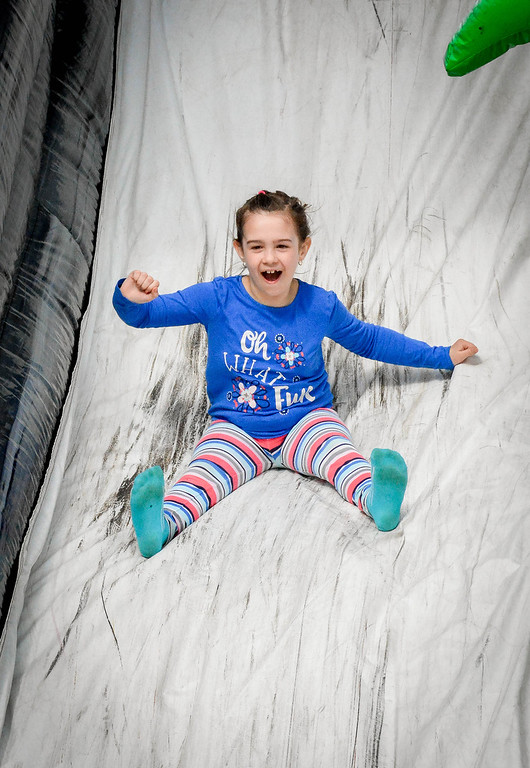 . Gabi Desjardins, 7, of Nashua has a blast on the blow up slide at the Lowell Winterfest on Saturday afternoon. SUN/Caley McGuane