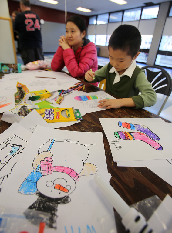 . 2017 Lowell Winterfest Saturday. Will Ren, 5, of Lowell, with his mother Yuan Shi, colors drawings that were the most wintry thing around. (SUN/Julia Malakie)
