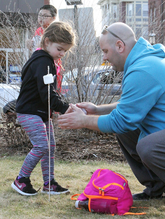 . 2017 Lowell Winterfest Saturday. Anthony Olenio of Haverhill wipes his daughter Sophie\'s hands as she eats toasted marshmallows. (SUN/Julia Malakie)