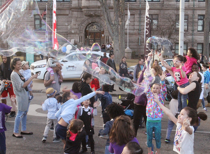 Kids try to reach big bubbles being released at 2017 Lowell Winterfest Saturday.  (SUN/Julia Malakie)