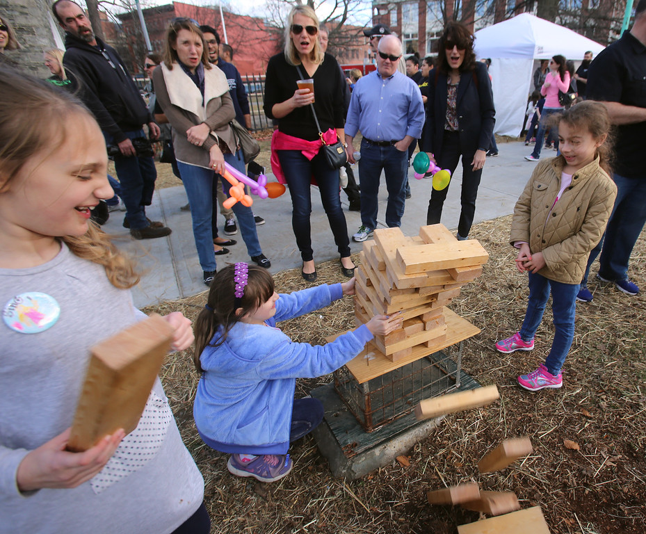 . 2017 Lowell Winterfest Saturday. From left, Sophia Mereves, 9, her sister Chloe Mereves, 8, of Lowell, and their cousin Martha Kapetanakis, 7, of Tewksbury, watch Jenga blocks tumble at Lucy Larcom Park.  (SUN/Julia Malakie)