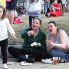2017 Lowell Winterfest Saturday. From left, Marley Rose Lavoie, 4, her mother Karrie McMurray, and McMurray's sister-in-law Jessica Hansen, all of Nashua, eat at the Ladd-Whitney monument triangle. (SUN/Julia Malakie)