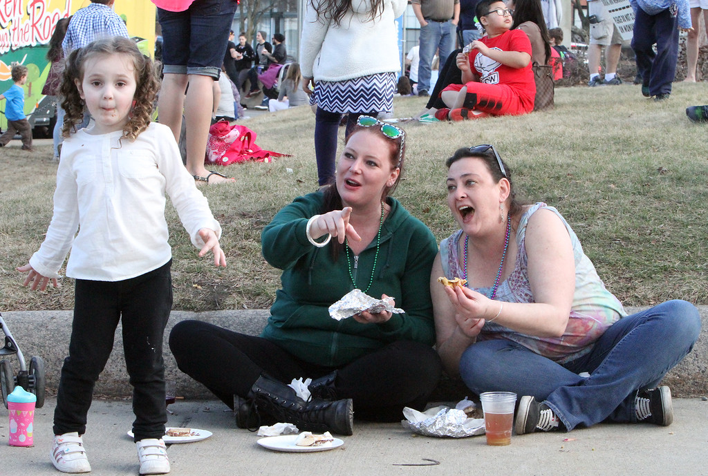 . 2017 Lowell Winterfest Saturday. From left, Marley Rose Lavoie, 4, her mother Karrie McMurray, and McMurray\'s sister-in-law Jessica Hansen, all of Nashua, eat at the Ladd-Whitney monument triangle. (SUN/Julia Malakie)