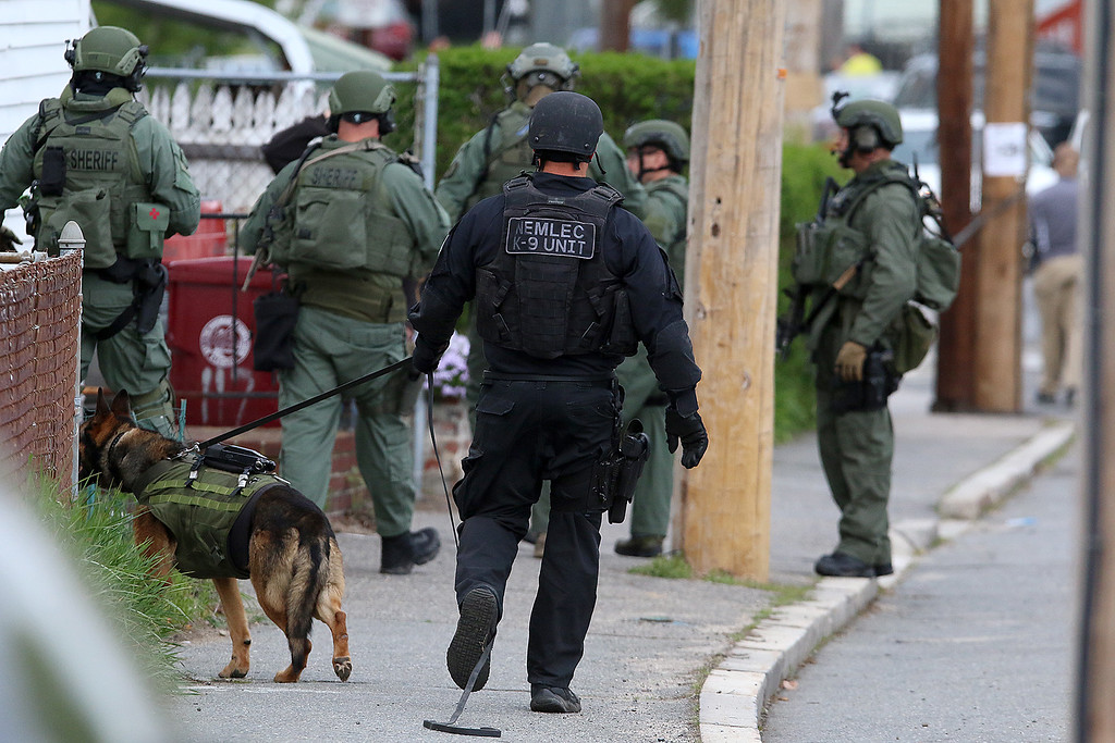 . Members of the North Eastern Massachusetts Law Enforcement Council (NEMLEC) and the Middlesex Sheriff\'s Office walks down Pine Street in Lowell as they search for Ross Elliott of Lowell who was a suspect in the killing of  a women early Thursday morning. SUN/JOHN LOVE