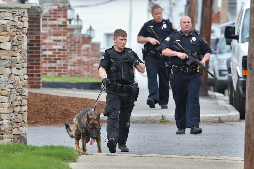 . Law enforcement officers walks down Pine Street in Lowell as they search for Ross Elliott of Lowell who was a suspect in the killing of  a women early Thursday morning. SUN/JOHN LOVE