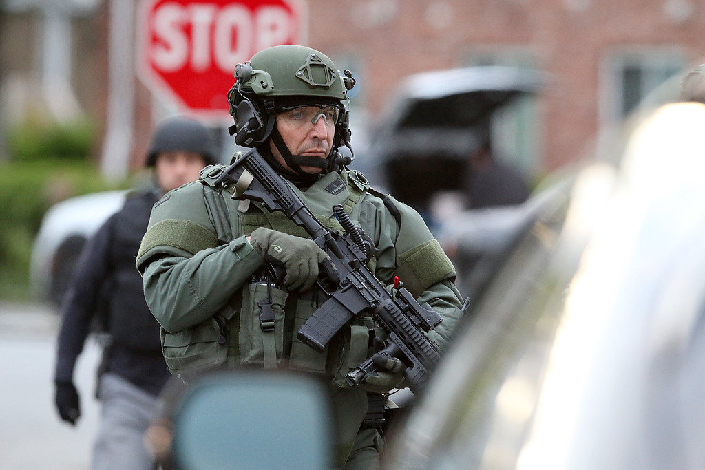 . A member of the North Eastern Massachusetts Law Enforcement Council (NEMLEC) walks down Pine Street in Lowell as he helps in the search for Ross Elliott of Lowell who was a suspect in the killing of a women early Thursday morning. SUN/JOHN LOVE