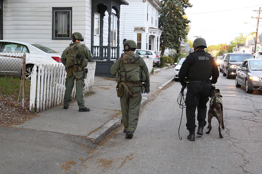 . Members of the North Eastern Massachusetts Law Enforcement Council (NEMLEC) and the Middlesex Sheriff\'s Office walks down Liberty Street in Lowell as they search for Ross Elliott of Lowell who was a suspect in the killing of a women early Thursday morning. SUN/JOHN LOVE