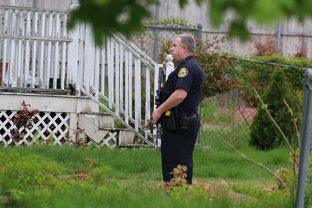. A police officer stands guard as they search for Ross Elliott of Lowell who was a suspect in the killing of  a women early Thursday morning in the Highlands area of Lowell. SUN/JOHN LOVE