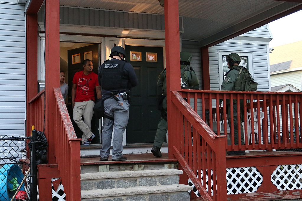 . Members of the North Eastern Massachusetts Law Enforcement Council (NEMLEC) and the Middlesex Sheriff\'s Office talk to a resident of Liberty Street in Lowell as they search for Ross Elliott of Lowell who was a suspect in the killing of a women early Thursday morning. SUN/JOHN LOVE