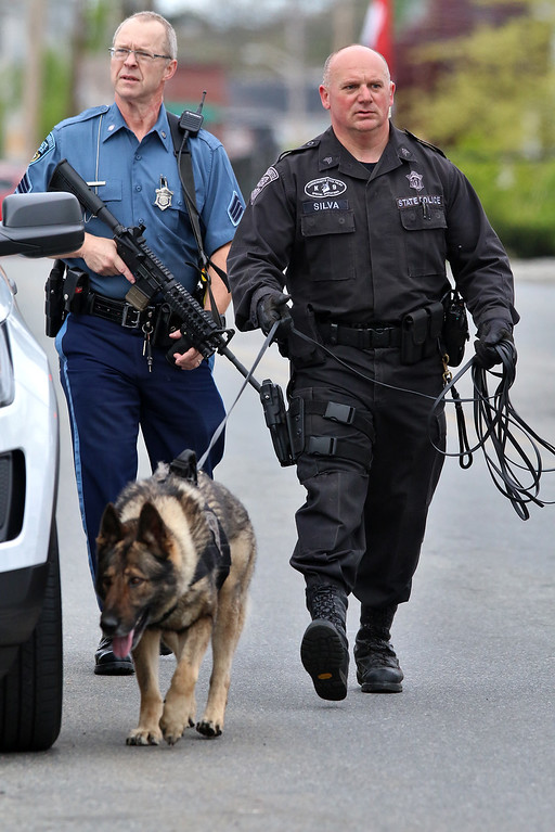 . State Police Troopers walks down Pine Street in Lowell as they search for Ross Elliott of Lowell who was a suspect in the killing of  a women early Thursday morning. SUN/JOHN LOVE