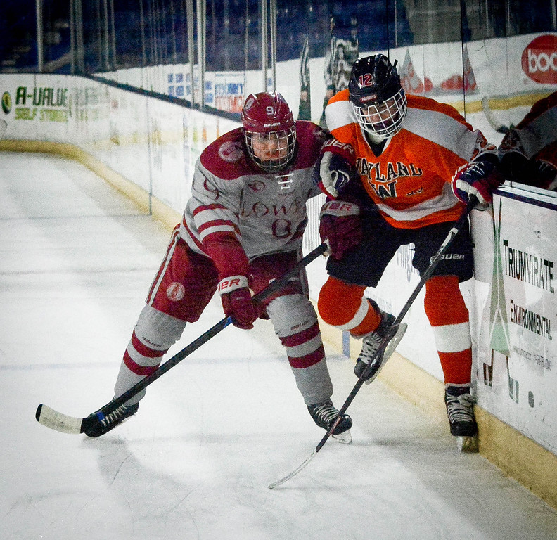 . At left, Lowell\'s Tyler Kotsifas body checks Wayland\'s Max Brande into the sideboard during their game at the Tsongas Center. SUN/Caley McGuane