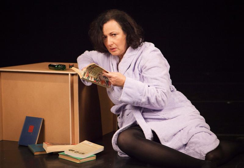 Caption:  Lucia contemplates her books to stop her panic.    Jeri Lynn Cohen. Photo credit: Julie Schuchard