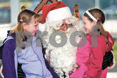 Andrew Skinner ¥ÊOceanaÕs Herald-Journal Taylor Ruggles, 8, left, and she sister Paige Ruggles, 6, sit with Santa Claus during annual tree lighting on the Pentwater Village Green Saturday evening, Nov. 28.