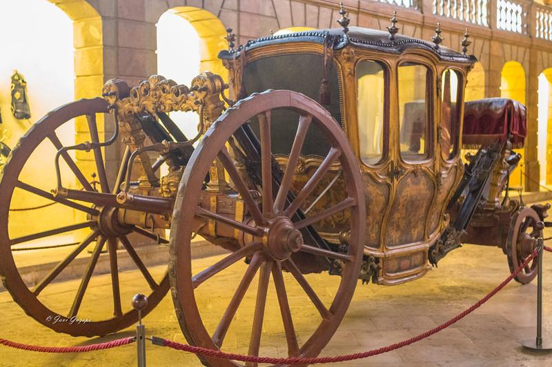 Colección de carruajes reales de los siglos XVI a XIX expuestos en un opulento palacio del siglo XVIII.
