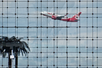 """Munich Dream"" © Falk Lumo 2010 -- Airplane taking off. Seen through Hotel Kempinski building's glass facade at Munich airport. The palms are inside the hotel lobby :)"