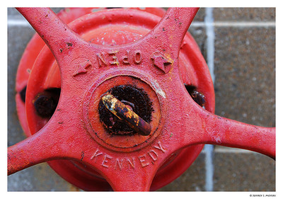 "Red Open Nikon D80 w/18-200 at 52mm (f7.1, 1/50, ISO 200)  My son saw me open this file and process it.  ""Why do you take pictures of stuff like that, Dad?""  ""Stuff like what?""  I asked.  ""Stuff like rusty pumps and yellow pipes and red wheels and crud.  It's weird.""  ""I guess I'm weird.""  ""Yeah. I guess so."""