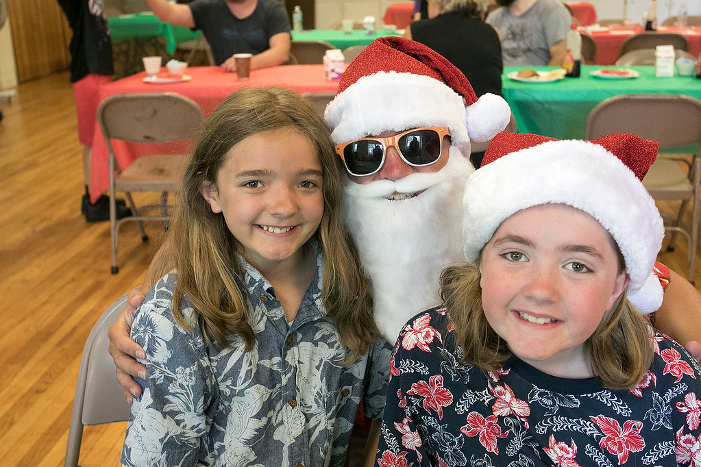 . Pancakes, sausage, fruit, juice, milk, and coffee was served at the Lunenburg Boys and Girls Club fundraiser Christmas in July with Santa Claus. Posing with Santa during the fundraiser is Saoirse Halligan, 11, and Shealeigh Halligan, 10, from Lunenburg. SENTINEL & ENTERPRISE/JOHN LOVE