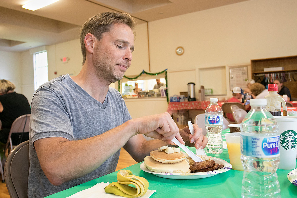 . Pancakes, sausage, fruit, juice, milk, and coffee was served at the Lunenburg Boys and Girls Club fundraiser Christmas in July with Santa Claus. Enjoying some pancakes at the fundraiser is Rob Shapiro of Lunenburg. SENTINEL & ENTERPRISE/JOHN LOVE