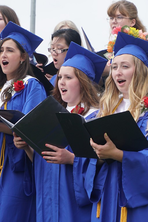 . Kaitlyn Coppenrath (left) and Taylor Jones sing to hundreds of people who gathered to watch them, and 92 other students graduate from Lunenburg High School on Saturday. (SENTINEL & ENTERPRISE / AMANDA BURKE)