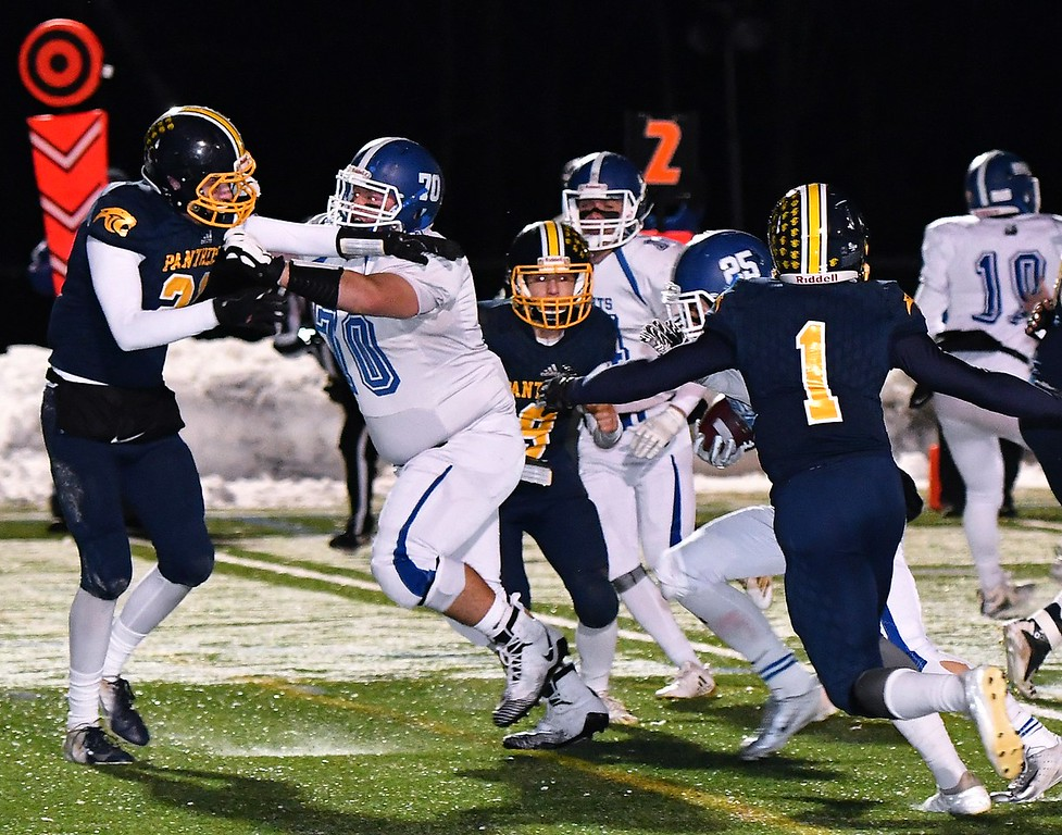 . #70, Joseph Nelson opens up a huge hole for Lunenburg\'s Cameron Mackenzie (#25). Sentinel & Enterprise / Jim Fay