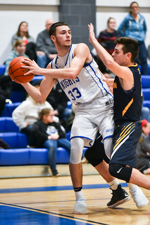 . (01/30/18 LUNENBURG MA) Lunenburg senior captain Connor Palma (left) passes the ball to the top of the key with pressure from Littleton defender in Tuesday night\'s game at Lunenburg High School.  SENTINEL & ENTERPRISE JEFF PORTER