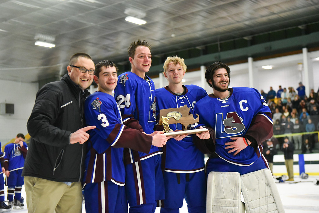 . (03/11/18 FITCHBURG MA) Left to right; Head coach Eric Short, senior Declan Fitzpatrick, senior Max Simmons, senior Brett Holman and senior goalie Nathan Bourdelais hold the MIAA Div. 3A Central boys hockey title after defeating Grafton at the Wallace Civic Center in Fitchburg on Sunday. SENTINEL & ENTERPRISE JEFF PORTER