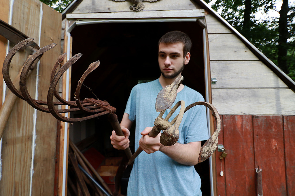 . Kevin Boussom, 18, talks about his new scrap metal art he is creating at his home in Lunenburg, Tuesday August 21, 2018. He picked up these old rusted rakes and said he wants to use them in a piece as claws. SENTINEL & ENTERPRISE/JOHN LOVE