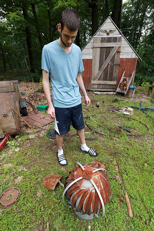 . Kevin Boussom, 18, talks about his new scrap metal art he is creating at his home in Lunenburg, Tuesday August 21, 2018. He shows of a roof vent he found that he has not found a use for yet but says he will. SENTINEL & ENTERPRISE/JOHN LOVE