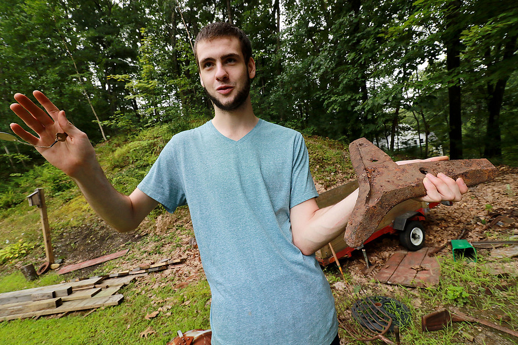 . Kevin Boussom, 18, talks about his new scrap metal art he is creating at his home in Lunenburg, Tuesday August 21, 2018. This is a piece to a plow that he picked up and thinks it will become a head to one of his pieces. SENTINEL & ENTERPRISE/JOHN LOVE