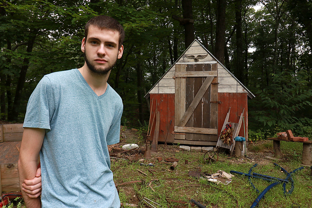 . Kevin Boussom, 18, talks about his new scrap metal art he is creating at his home in Lunenburg, Tuesday August 21, 2018. ypu can see a lot of stuff in his backyard, on the ground, that he has collected for his pieces. The shed behind him is also filled with his collected metal he may use to create more pieces. SENTINEL & ENTERPRISE/JOHN LOVE