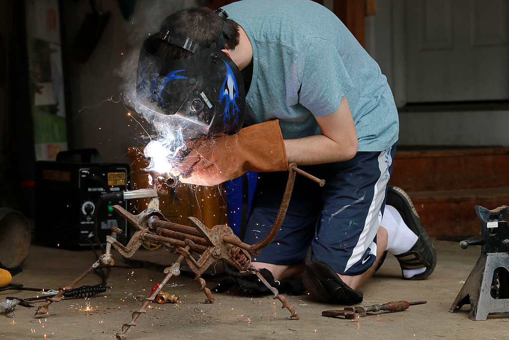 . Kevin Boussom, 18, talks about his new scrap metal art he is creating at his home in Lunenburg, Tuesday August 21, 2018. He works on his latest piece in his garage as he talks about his art. SENTINEL & ENTERPRISE/JOHN LOVE