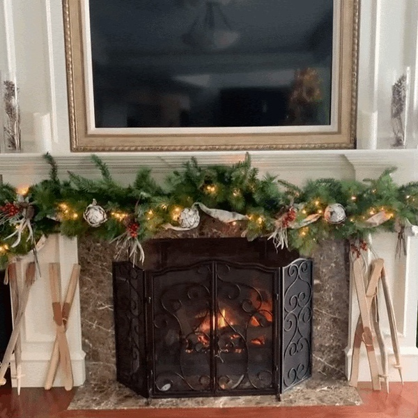The lustrous living-room fireplace is adorned with greens, lights, ribbons and ornaments, with an added touch of skis and ski poles on each side.