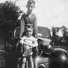 Luther Chesson and Parker Chesson standing on the front bumper of Jake Chesson's car. I believe the car was a 1941 Chevrolet.<br /> <br /> Photo was taken about 1944 or 1945. Not sure of the location, but probably at the Stokes farm where Granddaddy Chesson [Jesse Pyron Chesson] was living at that time.