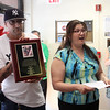Lynn, Ma. 6-21-17. Antonio Gutierrez,left, holding a plaque dedicated to the late Sean McCarriston as Teresa DiGregorio speaks at the opening of the new LYOSA office on Union Street.