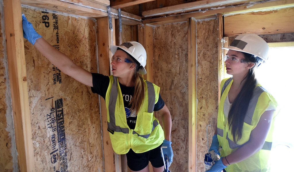 . Alora Cross, left, and Emily Van Leeuwen, do caulking on a new Habitat home.The youth service arm of the Lyons club is helping with the Lyons town home project, in coordination with Habitat for Humanity. They are working on homes damaged in the 2013 flood.  Cliff Grassmick / Staff Photographer/ June 30, 2018