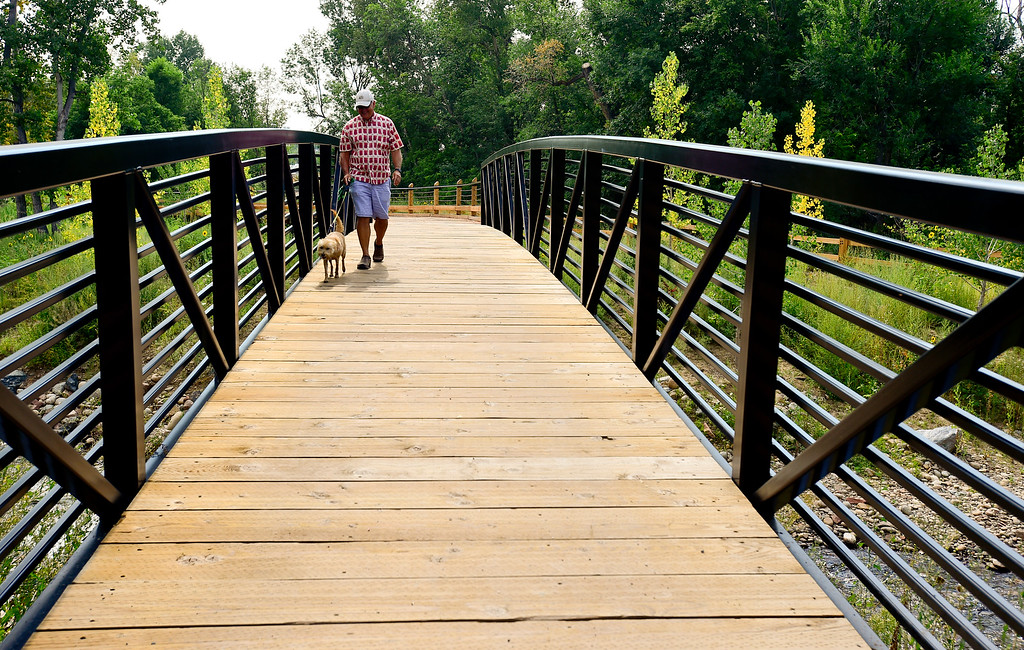 . LYONS, CO - AUGUST 17: Todd Anderson, of Lyons, walks his dog Sadie across a bridge at Bohn Park in Lyons on Aug. 17, 2018.  (Photo by Matthew Jonas/Staff Photographer)