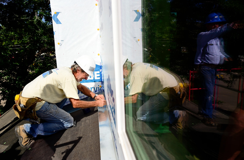 . LYONS, CO,  AUGUST 29: John Holloway, of Lyons, works on sealing flashing on a Habitat for Humanity duplex being built on the 100 Block of Park Street in Lyons on Aug. 29, 2018. The Park Street Development project is designated for families that survived the flood of 2013. (Photo by Matthew Jonas/Staff Photographer